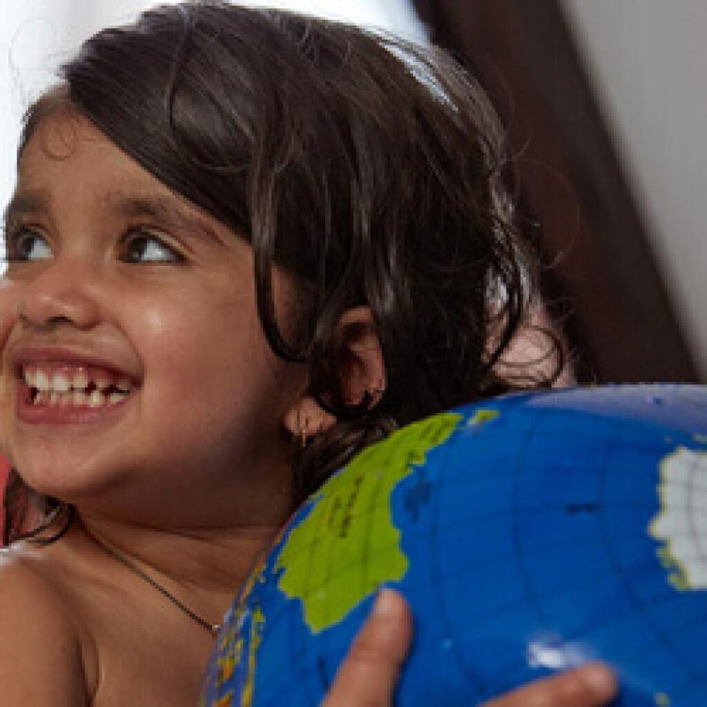 toddler holding globe in bath
