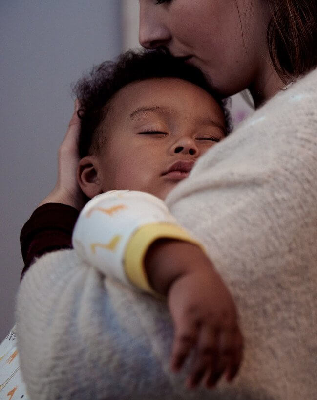 mom holding sleeping baby